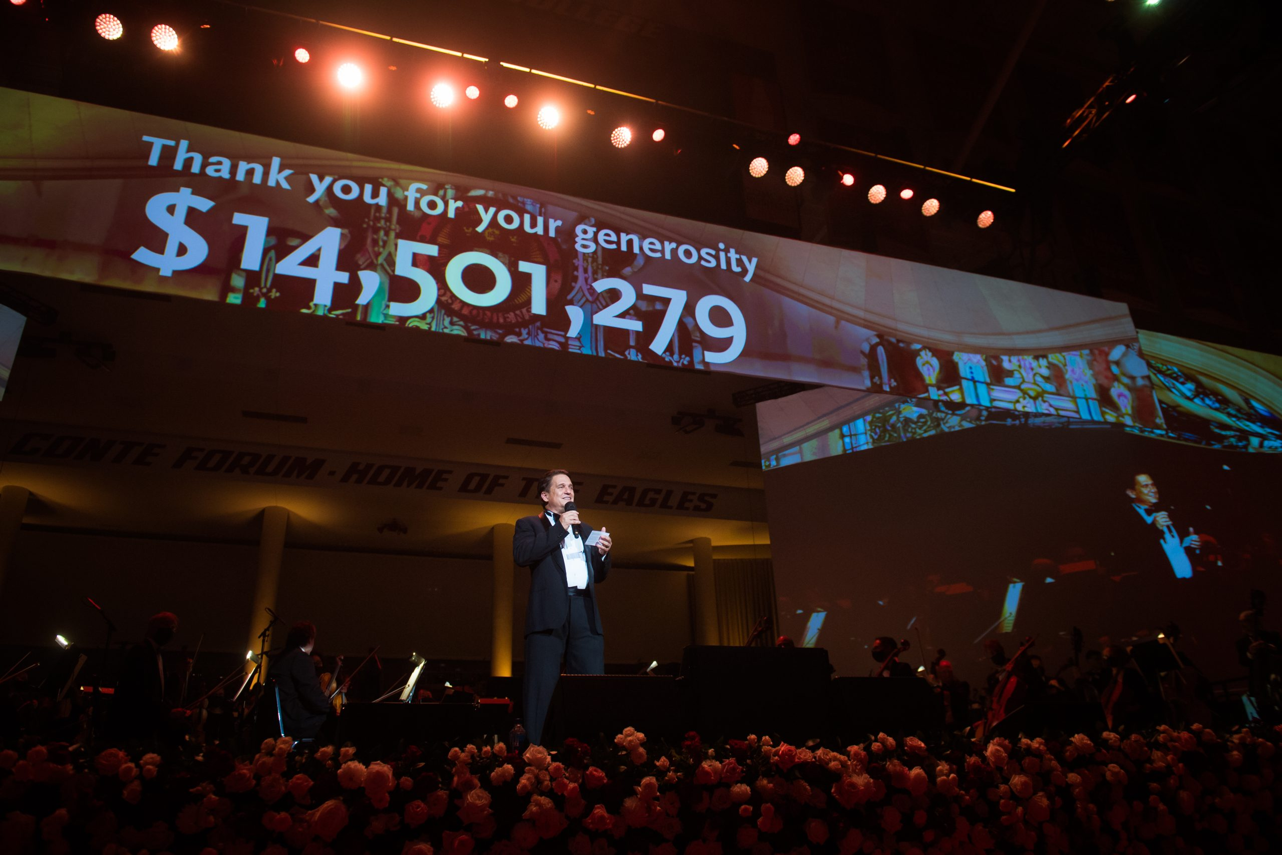 Keith Lockheart announcing to final total raised during the 29th annual Pops on the Heights at Boston College.